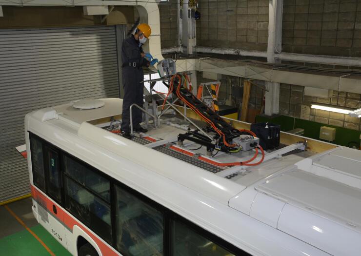 電気バスの急速充電用パンタグラフを点検する作業員