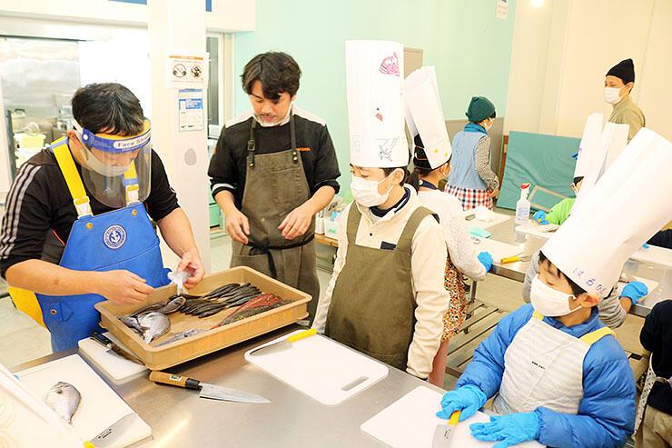 魚の多様さを紹介しながら、さばき方を子どもたちに指導する(左から)浜多さん、濱多さん=魚津総合公園無料休憩所