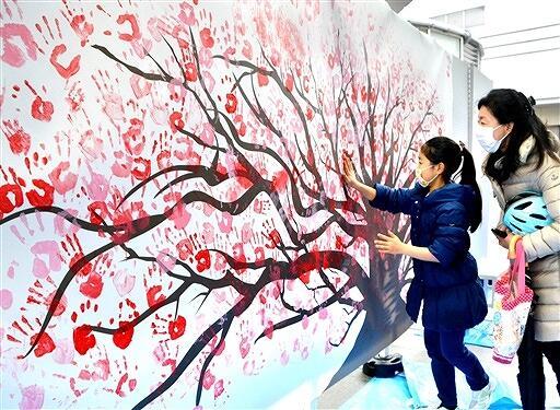 手形による桜のアートづくりに参加する親子=2月7日、福井県福井市のハピテラス