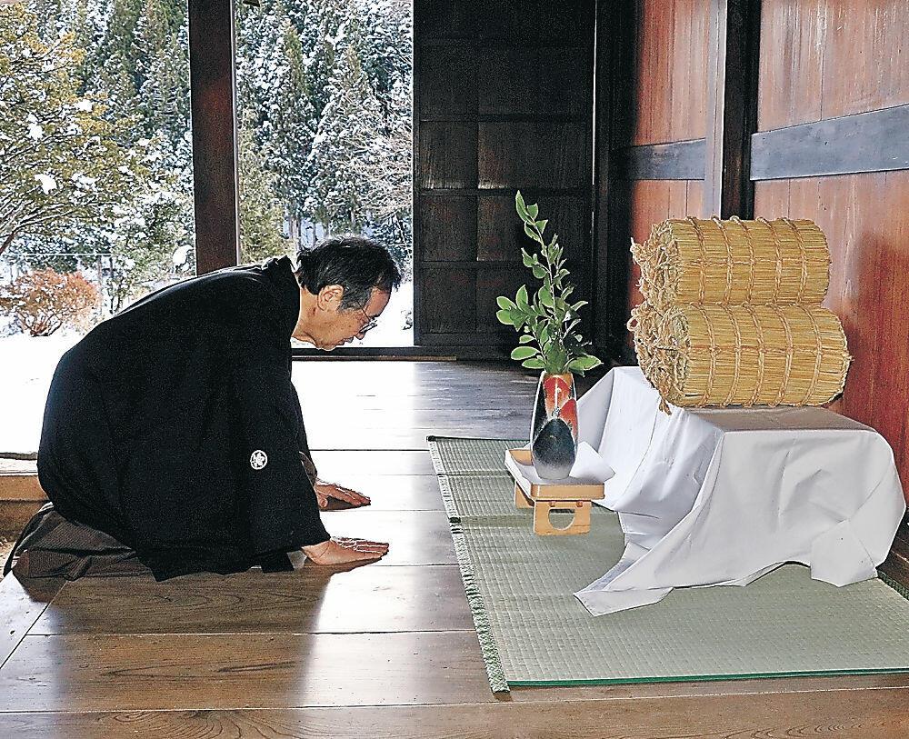 玄関先に田の神様を案内する吉村さん=能登町国重