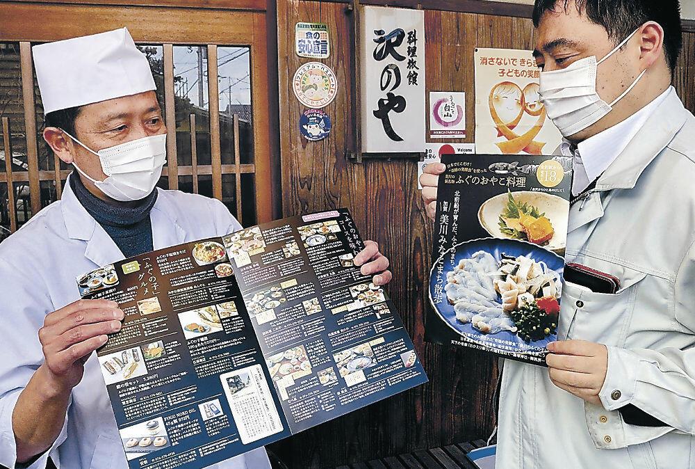完成したパンフレットを受け取る提供店舗の店主(左)=白山市美川南町