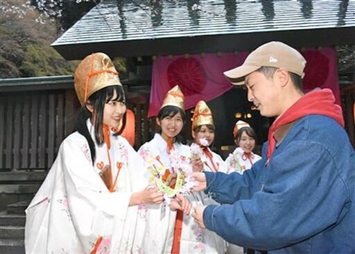 来場者と桜の小枝を交換する2019年の福娘ら=敦賀市の金崎宮