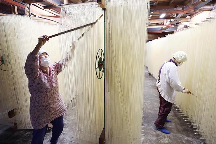 麺がくっつかないように箸で分ける作業をする黒田まさ子さん(左)=砺波市大門(吉田博昌撮影)