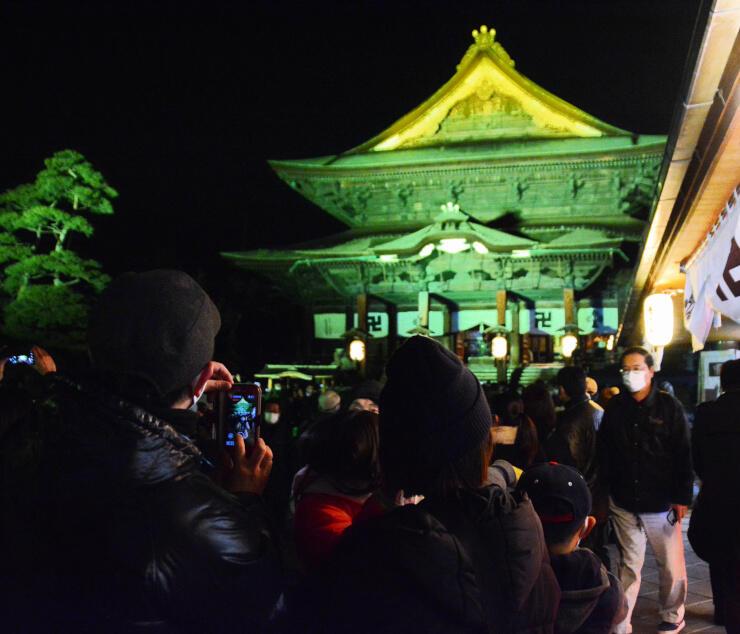 ライトアップされた善光寺本堂を撮影する人々
