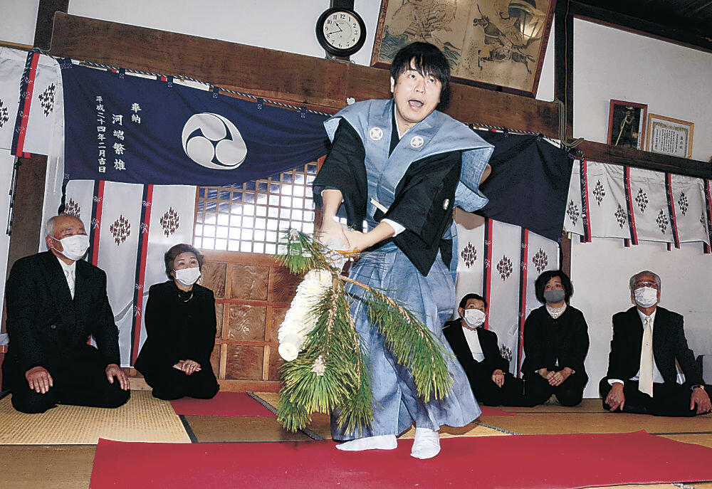 祝い棒と若松を手に舞を披露する岡本さん=輪島市門前町門前の櫛比神社