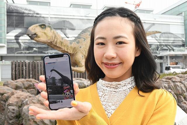 テレビドラマ「チア☆ダン」ゆかりの地を巡るデジタルスタンプラリーのアプリ。公式キャラクターと記念撮影もできる=JR福井駅西口の恐竜広場