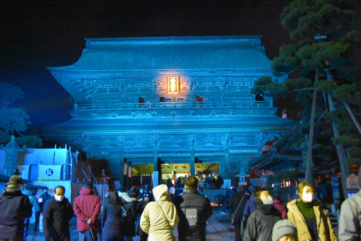 淡い青色にライトアップされた山門=11日午後6時21分