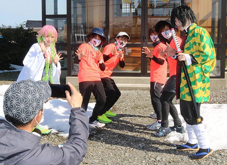 「鬼滅の刃」のコスプレーヤーと記念撮影を楽しむ参加者=滅鬼神明社