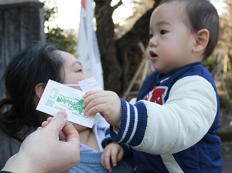 高岡城跡が描かれたシールを受け取る男児