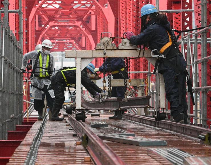 上田電鉄の千曲川橋梁で進む線路の敷設作業=15日午前9時37分、上田市
