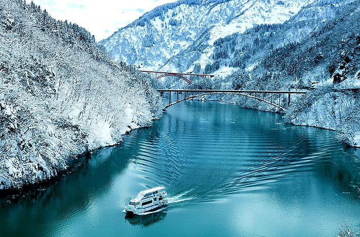 雪化粧した山々に囲まれた水面を進む遊覧船=庄川峡