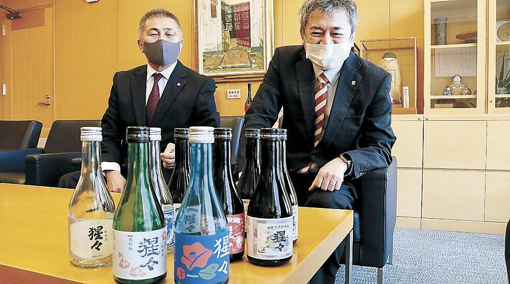 粟市長に猩々のラベルの候補を紹介する中村社長(右)=野々市市役所