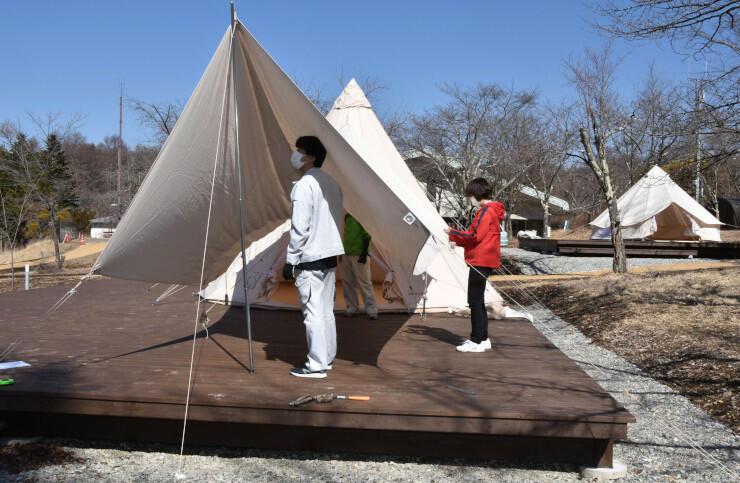 グランピング用のテントとタープを設置する村職員
