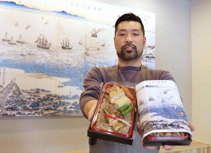 北前屋の看板商品「鶏めし弁当」を手にする店主の片桐誠司さん=新潟市東区