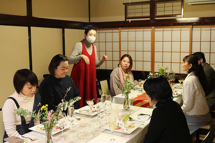沢樹さん(左から3人目)から料理の説明を受ける参加者=内川の家奈呉