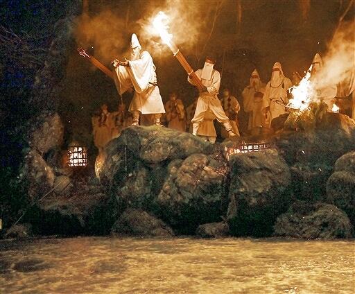 炎に照らされる中、遠敷川に御香水を注いだお水送り=3月2日午後8時45分ごろ、福井県小浜市下根来の鵜の瀬