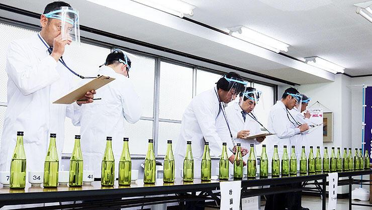 新酒を口に含んで、味や香りを確かめる審査員=県酒造組合事務所