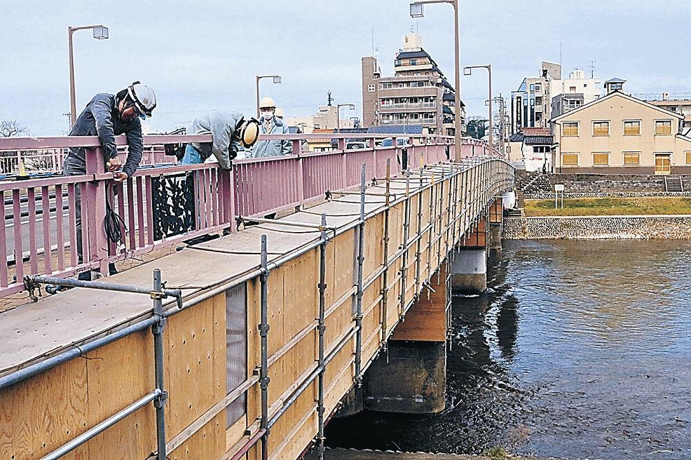 桜橋で照明の設営作業を進める作業員=金沢市清川町