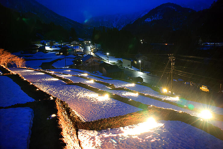 ライトアップされた雪が残る石積み棚田。奥は楮集落=南砺市楮