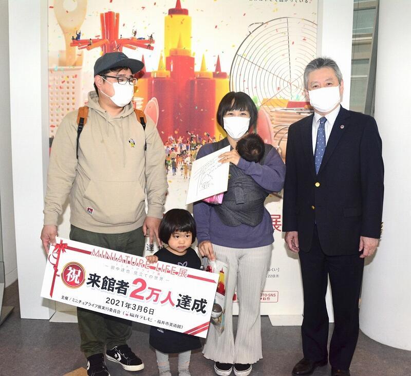 記念品を受け取る2万人目の家族=3月6日、福井市美術館