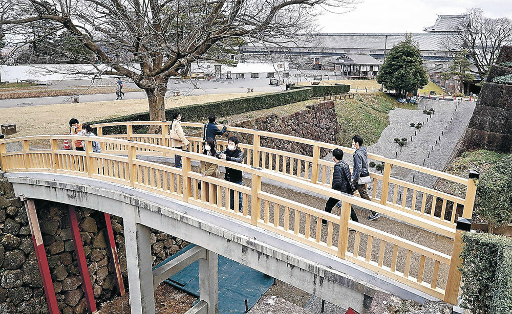 20年ぶりに欄干が改修された極楽橋を渡る来園者=金沢城公園