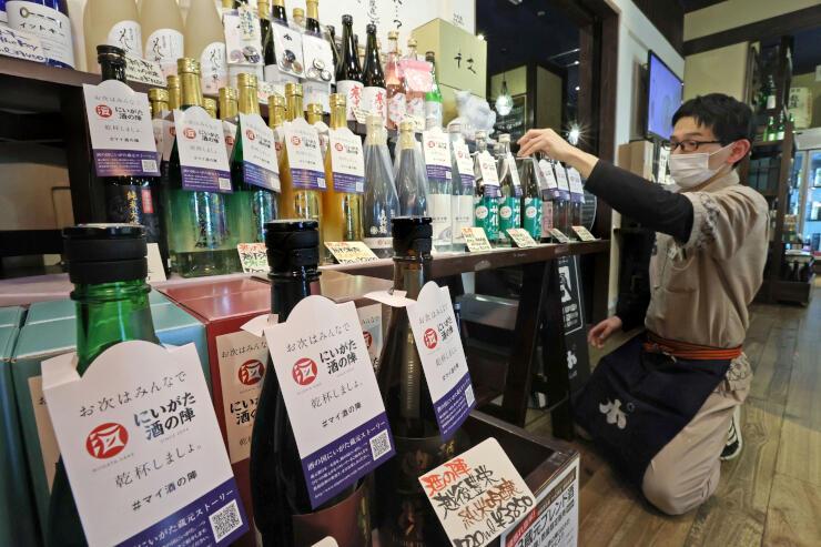 「にいがた酒の陣」のラベルや首掛け付きの限定酒が並ぶ売り場=新潟駅の「ぽんしゅ館」