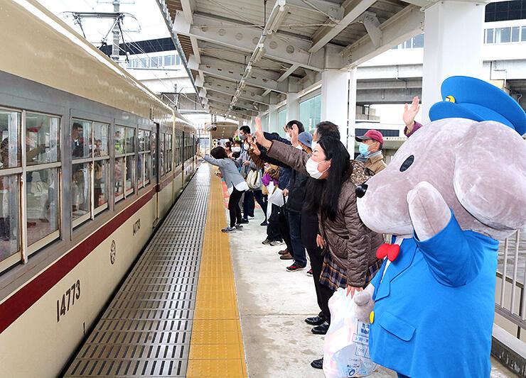 園児らを乗せて出発する電車を見送るくろワン(右)ら=富山地鉄新黒部駅