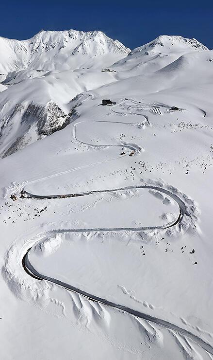 除雪され、雪原に曲線を描く天狗平付近の高原バス道路=15日午後0時半ごろ、本社チャーターヘリから