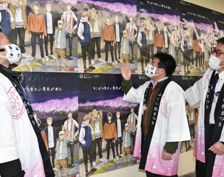 長野電鉄長野駅に掲示された「ふくい桜まつり」のポスターを確かめる福井市観光協会の職員ら