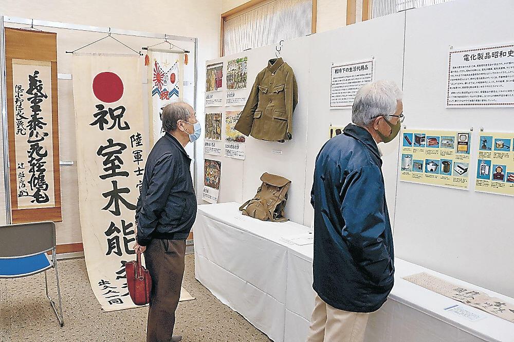 展示された遺品や資料に見入る来場者=金沢市の石川護国神社