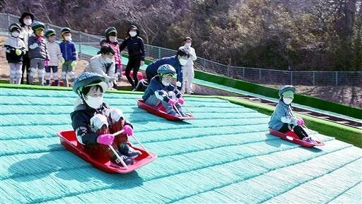 人工芝のちびっこゲレンデでそり遊びを楽しむ園児たち=3月18日、福井県敦賀市総合運動公園