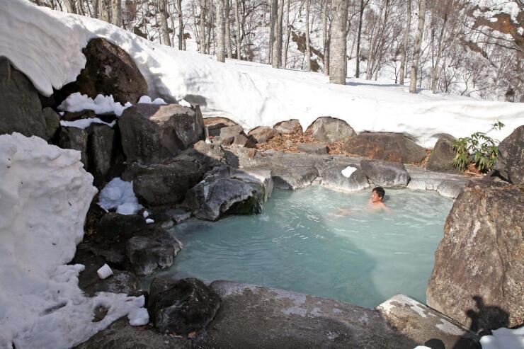 雪が残る中、ことしのオープンを迎えた「黄金の湯」=20日、妙高市