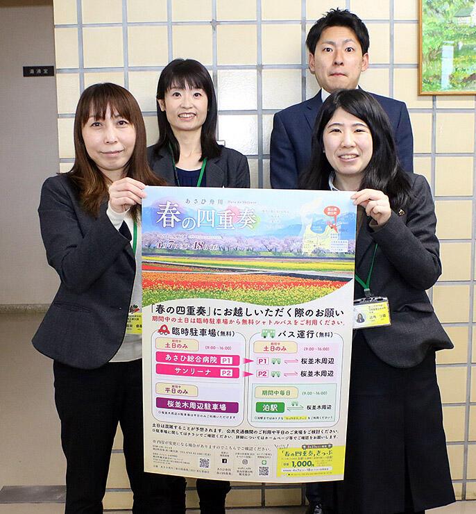 ポスターを掲げ、シャトルバスや公共交通の利用を呼び掛ける朝日町職員