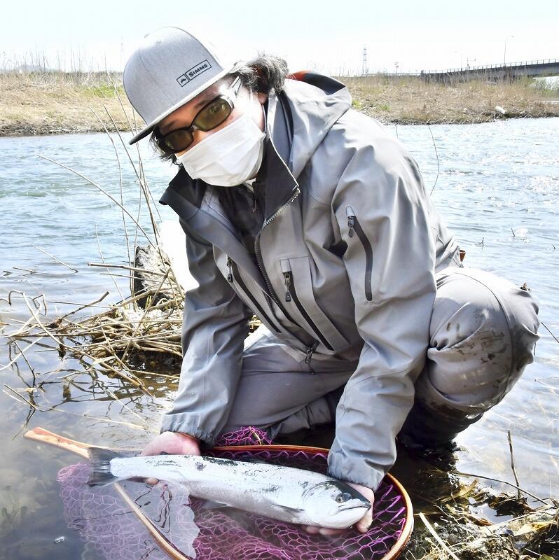 今シーズン初のサクラマスを釣り上げた中村さん=3月27日、福井県鯖江市石田下町