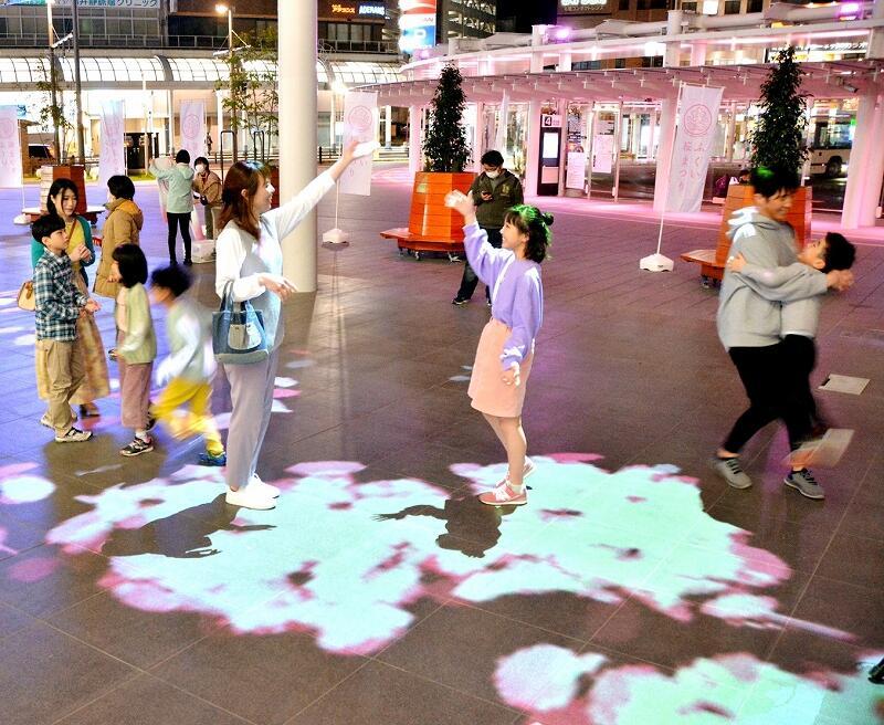 桜の花びらの映像が投影されるプロジェクションマッピングを楽しむ親子連れ=3月27日、福井市のハピテラス