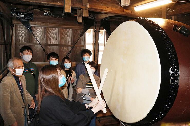 修復された太鼓をたたいて完成を祝う若者(手前)=高岡市伏木古国府