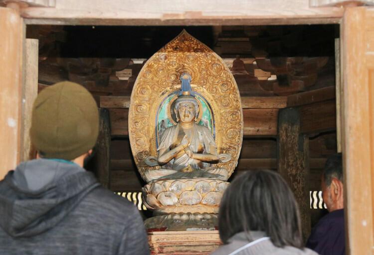 公開された安楽寺の大日如来坐像を見る参拝者