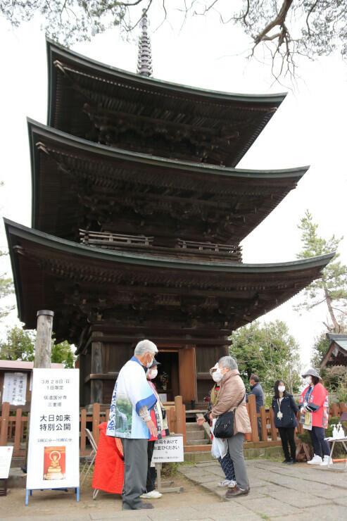 信濃国分寺の三重塔の前で大日如来坐像などの説明を聞く人たち