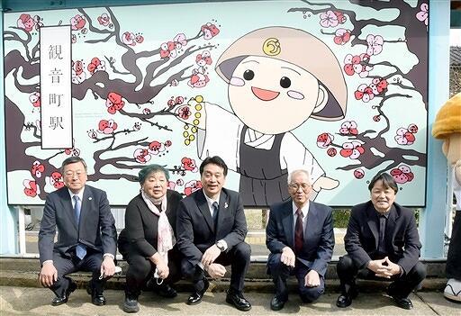 完成した看板を前に記念撮影する関係者=3月30日、福井県永平寺町のえちぜん鉄道観音町駅
