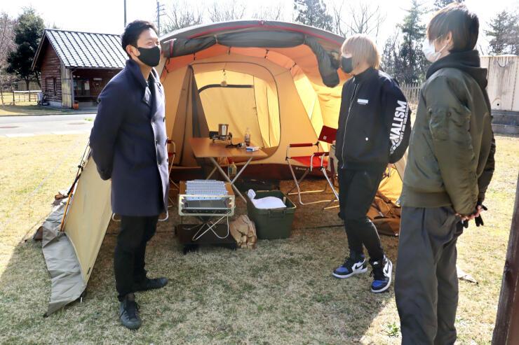 宿泊するテントを前に打ち合わせするスタッフ=佐渡市山田
