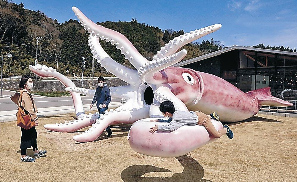 イカのモニュメントで遊ぶ親子連れ=能登町越坂のイカの駅つくモール