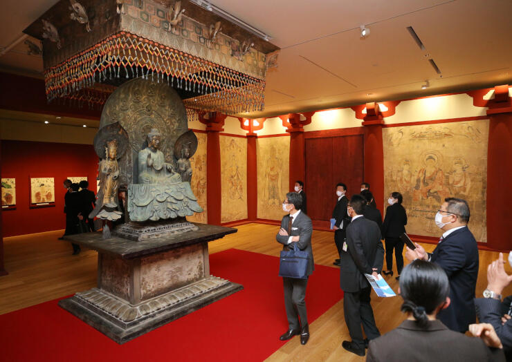 完成記念展で展示される国宝・釈迦三尊像の復元像を鑑賞する関係者=9日、長野市の長野県立美術館