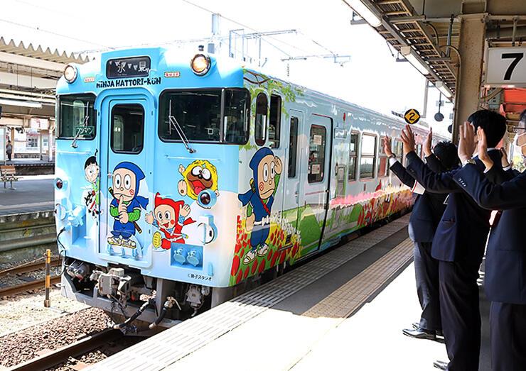 関係者に見送られて出発する「忍者ハットリくん列車」の新車両=高岡駅