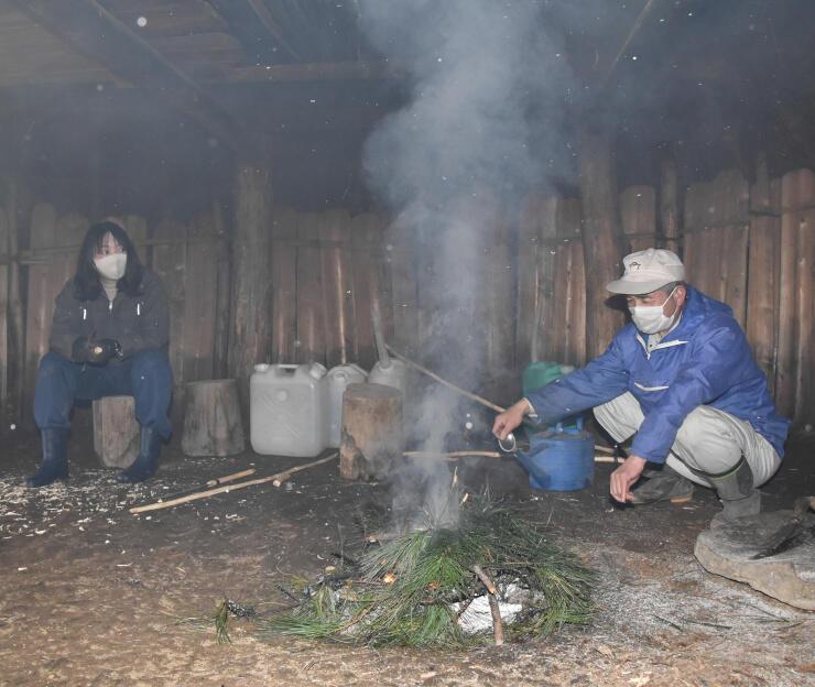 復元住居内で松の葉を燃やす学芸員ら
