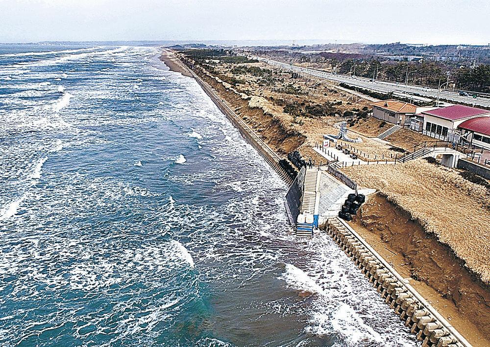 浸食された千里浜なぎさドライブウェイ=2月21日、宝達志水町柳瀬(小型無人機から)