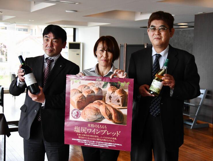 レストランで提供するパンのチラシとワインを手にする関係者たち