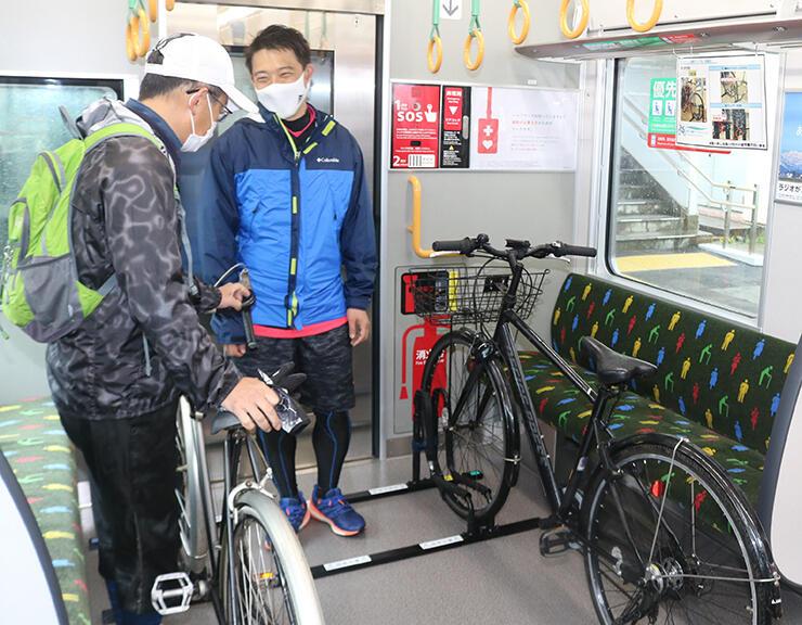 専用のラックに自転車を固定する利用客=東富山駅