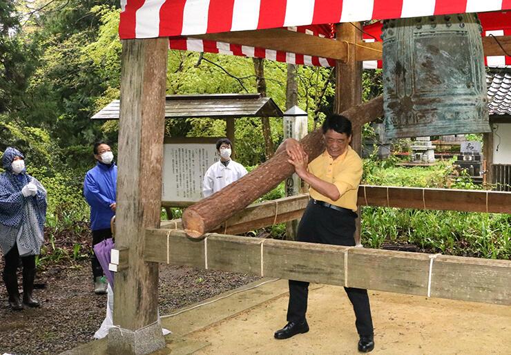 関係者が見守る中、丸太を担いで懸命に鐘を突く参加者=上日寺