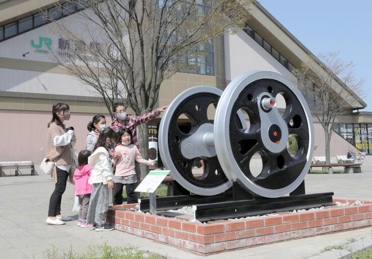 D51の動輪を眺める親子連れら=新潟市秋葉区のJR新津駅東口広場