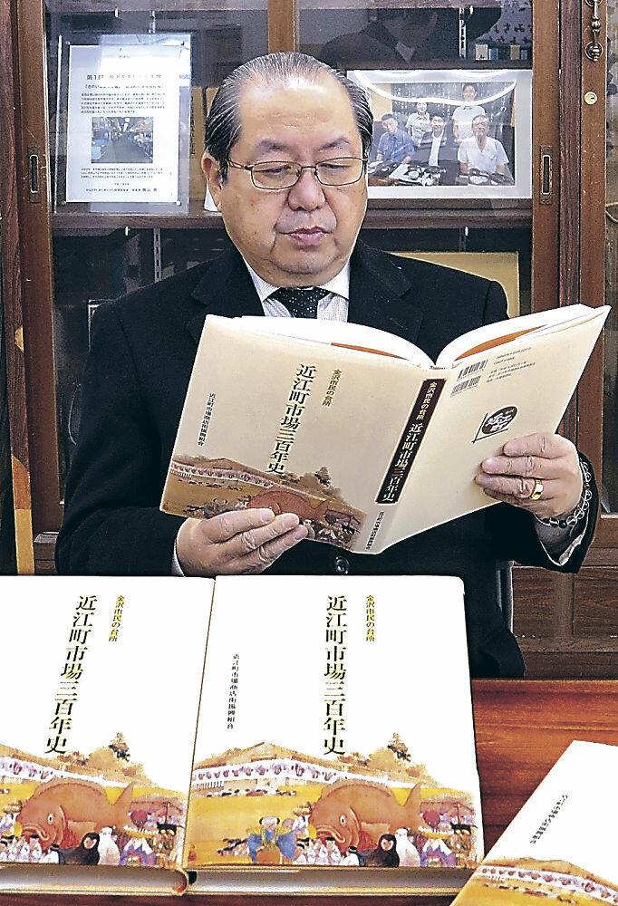 完成した「近江町市場三百年史」を眺める吉村理事長=金沢市上近江町